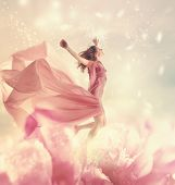 Beautiful Young Woman Jumping On Giant Flower