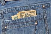 Close up dollar bills in jeans pocket