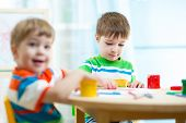 kids painting in daycare or nursery or playschool