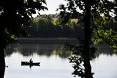 foto of canoe boat man  - fisherman in boat in summer day. fishing on lake