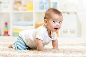 stock photo of crawl  - crawling funny baby boy indoors at home - JPG