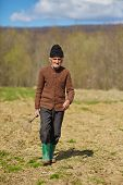 picture of hoe  - Senior man with a hoe in his hand walking to a field - JPG