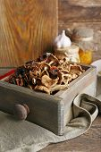 foto of wooden crate  - Dried mushrooms in crate on wooden background - JPG