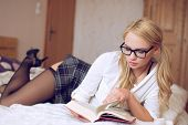 stock photo of clever  - Sexy clever woman reading book in college - JPG