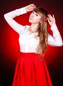 stock photo of chemise  - Beautiful young woman in a white chemise and a red skirt over bright red background - JPG