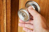 image of wooden door  - Male hand opening shining metal door handle in closed wooden door photo with selective focus and shallow DOF - JPG