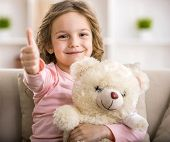 picture of teddy  - Handsome little girl is sitting on sofa with teddy bear and shows thumb up - JPG