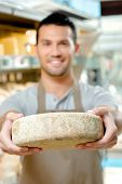 stock photo of meals wheels  - Man holding a wheel of cheese - JPG