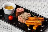 foto of veal  - Veal sauce with vegetables in a restaurant on a dark plate - JPG