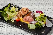image of veal  - Veal sauce with vegetables in a restaurant on a dark plate - JPG
