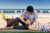 picture of couple sitting beach  - Portrait of young asian couple enjoy holiday at the beach sitting on mat while looking at each other with lovely - JPG