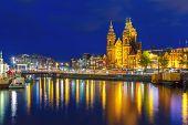 stock photo of saint-nicolas  - Night city view of Amsterdam canal and Basilica of Saint Nicholas - JPG