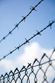 image of barbed wire fence  - barbed wire fence with sky and cloud background - JPG