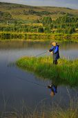 stock photo of trout fishing  - Lady fly fishing, calm water, late afternoon ** Note: Visible grain at 100%, best at smaller sizes - JPG