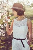 stock photo of wearing dress  - Portrait of young woman in the flowered field in the spring time - JPG