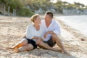foto of couple sitting beach  - young attractive and beautiful American couple in love sitting on the beach the man hugging woman lying on wet sand smiling happy in romantic summer holidays - JPG