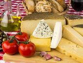 stock photo of cheese platter  - Assorted cheese olives tomatoes and other ingredients typical of the Mediterranean diet - JPG