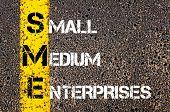 foto of enterprise  - Business Acronym SME as Small Medium Enterprises. Yellow paint line on the road against asphalt background. Conceptual image - JPG