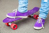 pic of skateboarding  - Young skateboarder in gumshoes and jeans stands - JPG