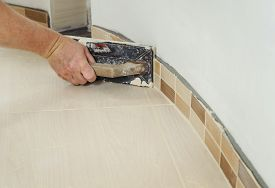 pic of grout  - The hand of man holding a rubber float and filling joints with grout - JPG