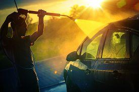 stock photo of pressure-wash  - Vehicle Washing at Sunset Hot Summer Afternoon Car Washing - JPG