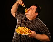 Diet failure of fat man eating fast food . Overweight person who spoiled healthy food by eating fren poster