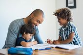 Young black father helping his boys with homework. Multiethnic brothers studying with their dad at h poster