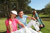 Couple sitting on a golfcourse