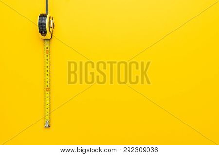 poster of Tape Measure On The Yellow Background. Photo Of Yellow Tape Measure With Copy Space. Top View Of Met