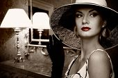 Beautiful woman in hat in luxury interior.