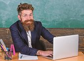 Back To School Concept. Writing School Report. Teacher Bearded Hipster With Eyeglasses Sit In Classr poster