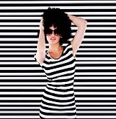 Funky lady in striped top with afro hairstyle standing in front of striped black and white background creating a bold optical illusion.