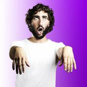 young man imitating a zombie against a purple background