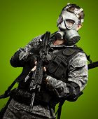 portrait of a young soldier with a gas mask and a rifle against a green background