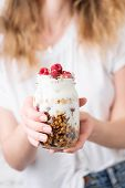 Yogurt With Granola And Berries In Jar In Female Hands. Blonde Woman In White Shirt Holding Jar Of Y poster