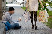 stock photo of beggar  - Beggar and a rich young woman with shopping bags - JPG