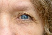 Close Up Of One Pale Blue Eye Of Middle Age Woman With Wrinkles. Full Frame Detailed Portrait poster