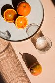 Pears and oranges with  art shadows on a color backround. Artistic healthy breakfast on a table. Sti poster