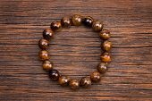 Bracelet From Round Stones Lying On A Wooden Background. Bracelet From A Natural Dark Stone. Jewelry poster