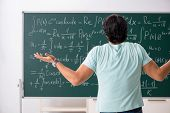Young male student mathematician in front of chalkboard  poster