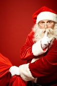 Portrait of Santa Claus with huge red sack keeping forefinger by his mouth and looking at camera