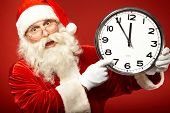 Photo of Santa holding clock showing five minutes to midnight and warning about forthcoming Christma