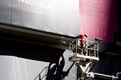 NEW YORK - OCT 18: Two workers on a motorized lift install an advertising billboard for Microsoft in