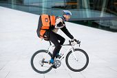 Young male cyclist with courier delivery bag riding bicycle
