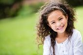 stock photo of windy  - Sweet little girl outdoors with curly hair in the wind - JPG