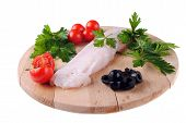 cod steak with tomatoes olives and parsley isolated on white
