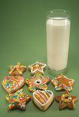 stock photo of ginger bread  - Christmas cookies and a glass of milk isolated against green paper - JPG