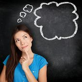 Woman thinking blackboard concept. Pensive girl looking at thought bubble on chalkboard / blackboard