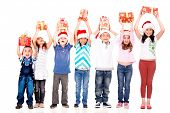 Excited children holding Christmas gifts with arms up - isolated over white