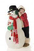 An adorable preschooler in outside winter wear snuggling up with a snowman dressed for Christmas.  On a white background.